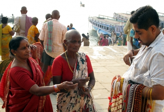 A woman with her head shaved in ritual mourning buys beads