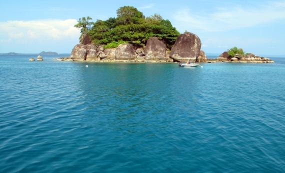 Blue water surrounds an island reef