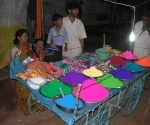 A family sell coloured powder before Holi