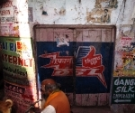 A Brahmin and a pariah dog pass by a door painted in the colours of Thums Up, India's spicy cola