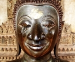 A defaced Buddha in the galleries at Wat Haw Phra Kaew