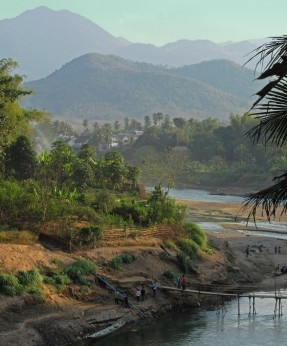 The Nam Khan, with bamboo on its banks and rolling hills behind it