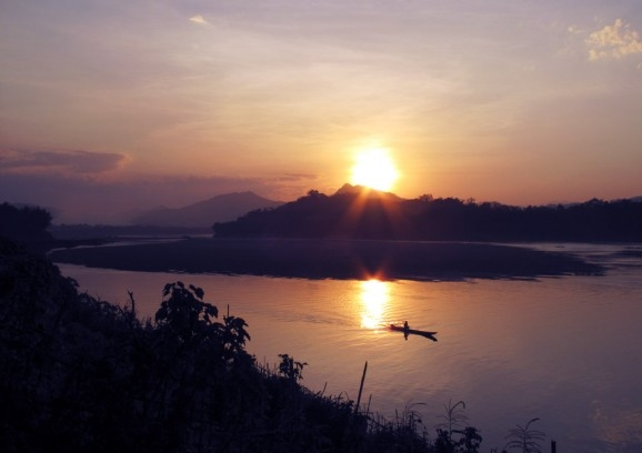 The sun sets behind the limestone hills that surround Luang Prabang