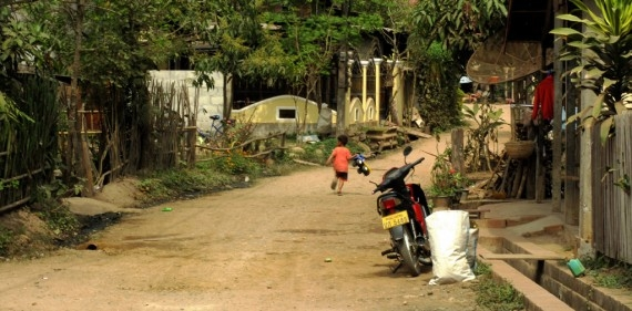 A child runs through Ban Pha Nom's dirt roads
