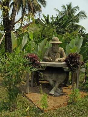 A statue of Henri Mouhot writing barefoot