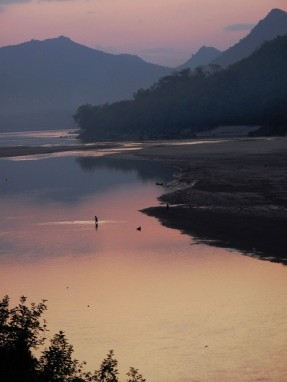 A solitary fisherman wades knee-deep through the Mekong at dusk